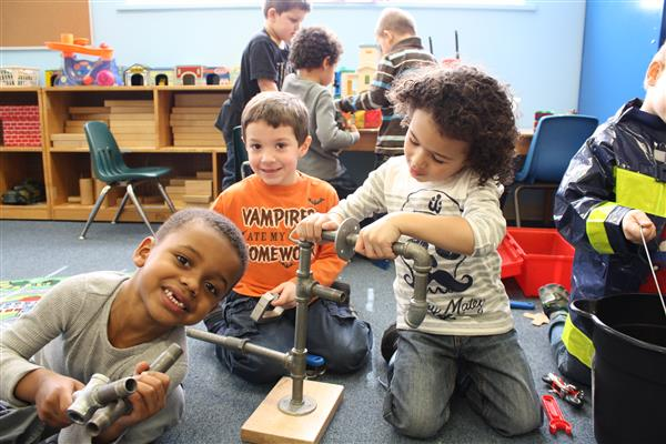 Three preschool boys playing with educational toys in classroom