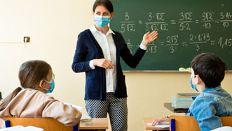 Teacher wearing a mask and teaching students in a classroom.