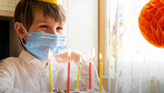 Young boy wearing a mask at his birthday party.
